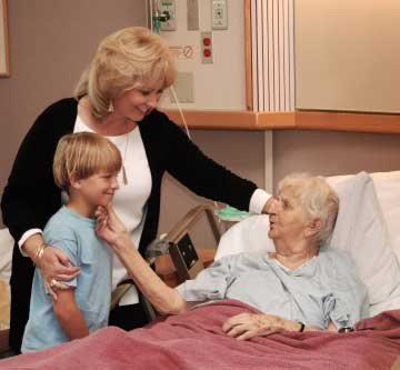 Elderly woman in hospital being visited by relatives
